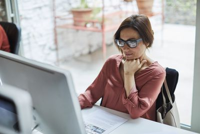 Person wearing glasses, sitting at a desk