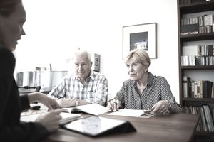Senior couple listening to their female financial consultant at home. Elderly couple at home meeting with financial advisor.
