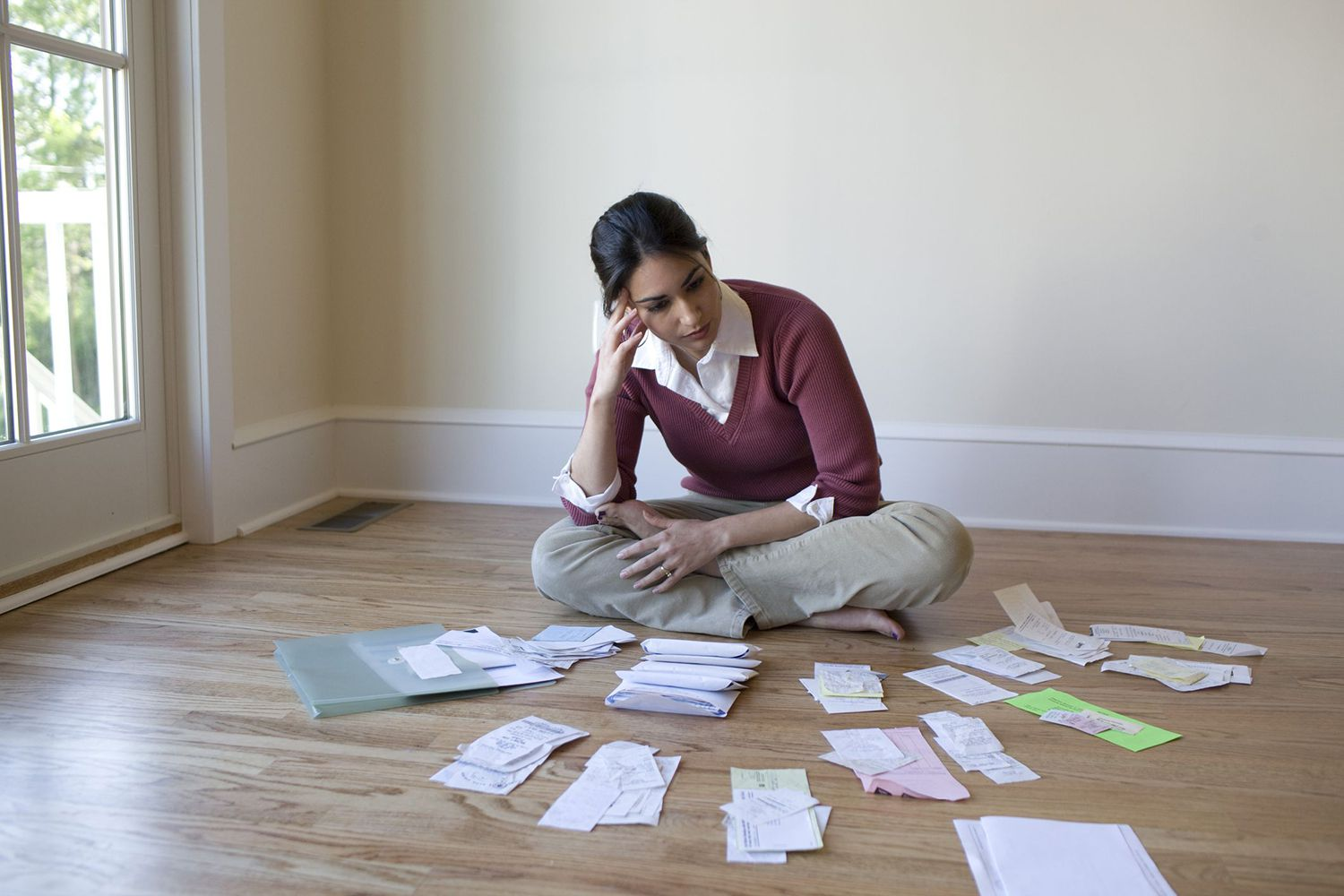 A Woman Sitting on a Hardwood Floor Surrounded by Bills