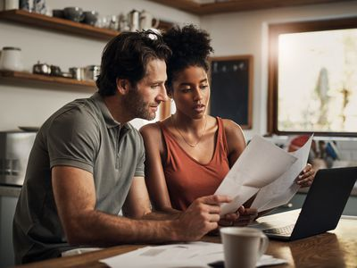 Couple looking at statements and working on laptop