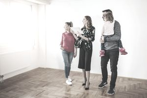 A couple with a young child and a realtor look out a window in an empty room.