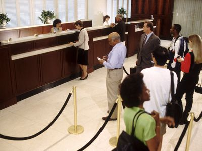 Bank customers wait in line to see a representative
