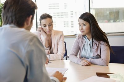 Couple discussing a real estate contract with agent