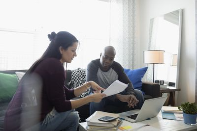 Couple at laptop discussing paperwork paying bills online in living room