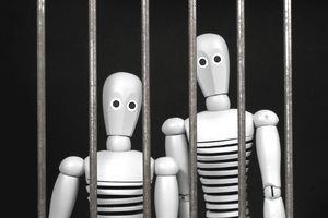 Two dummies looking out through bars