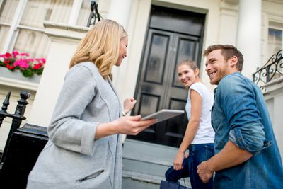 Happy couple with real estate agent entering a house