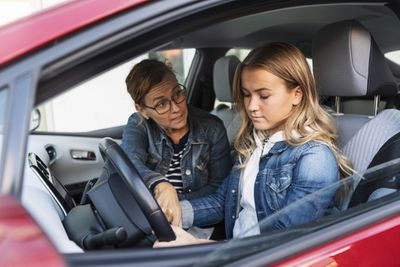 Woman in car passenger seat teaches teenager to drive
