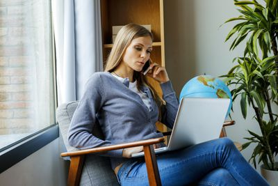 Woman in Armchair Gazes at Laptop With World Globe at Her Elbow