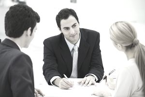 Man in suit meeting with a couple over a desk