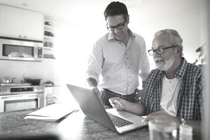 Son helping senior father paying bills at laptop in kitchen