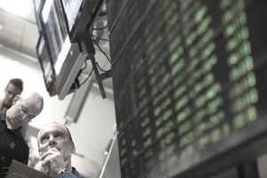 A stock broker rest his chin on his hand with screens surrounding him.