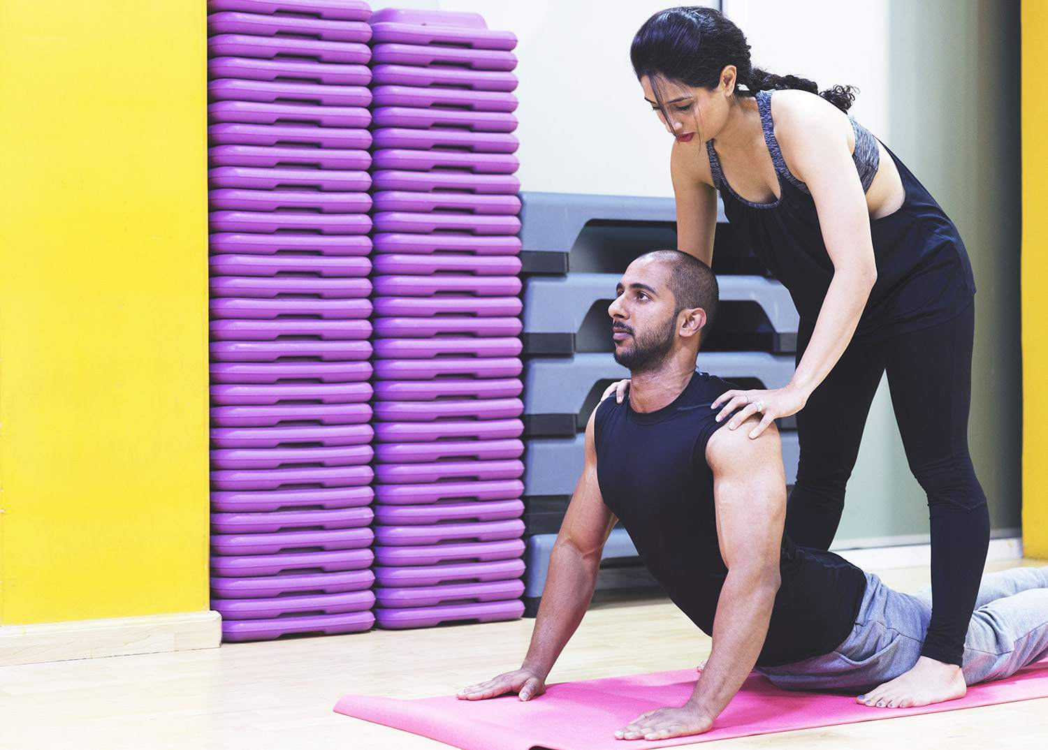 Personal Trainer Assisting Student With Cobra Pose in Her Yoga Class