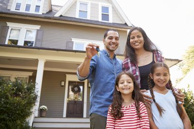 Portrait of family holding keys to new home on move-in day