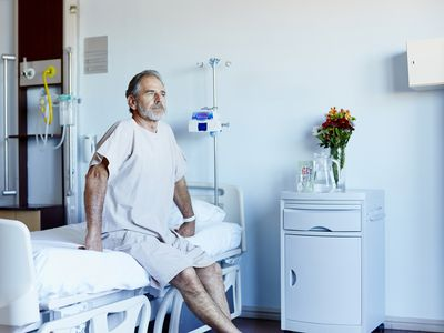 Mature man sitting on bed in bright hospital room