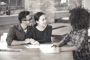A couple working with a financial advisor in an industrial office.