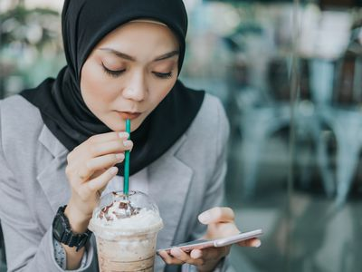 Woman drinking frothy coffee while working on smartphone