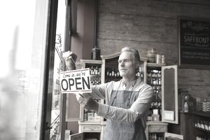 Man places an open sign in the front window