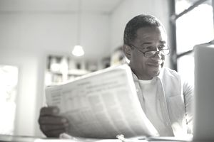 Senior man with newspaper using laptop