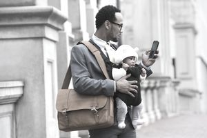 millennial father with baby in a carrier stops to look at his phone on a city street