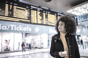 A young woman in an airport by the arrivals and departures screen