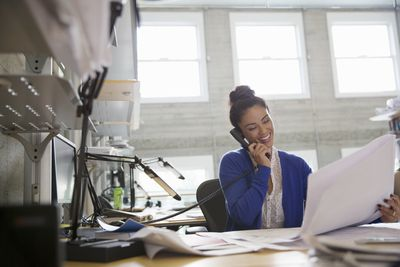 Businesswoman using phone and reviewing drawings in modern office