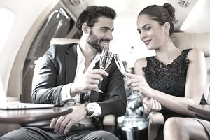 Couple of people having a champagne toast inside the private jet airplane