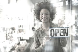 Woman standing behind Open sign in a store window