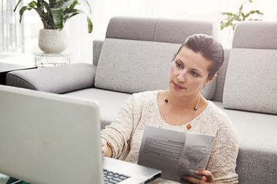 A woman visits the IRS website on a laptop to check on the status of her plus-up payment.