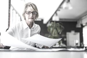 women with short blond hair and glasses looking at paperwork in home office