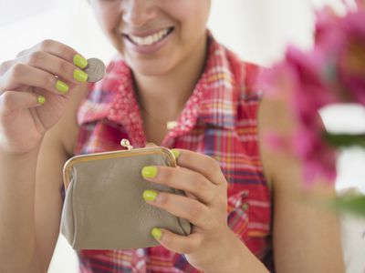 Woman putting money in purse saving money from insurance