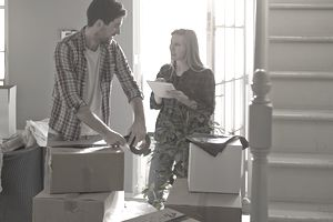 A young couple packing boxes after selling their home