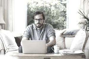 Man sitting on sofa and using laptop at home