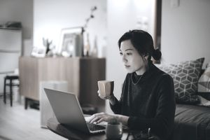 Busy concentrated young Asian woman working from home, working on laptop till late in the evening at home. Home office, overworked, deadline and lifestyle concept