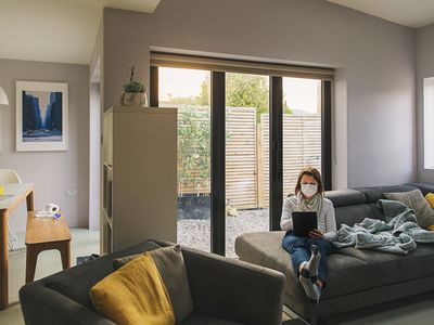 Image shows a woman social distancing in her home, wearing a facemask on her ipad.