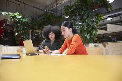 two people at a table looking at their phones in a room full of plants