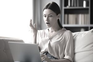Shocked young woman with open mouth looking with amazement at laptop screen