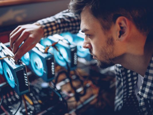 Man preparing a cryptocurrency data mining rig