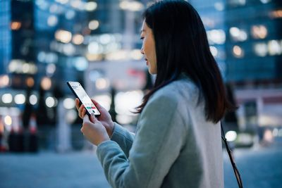 Young Asian businesswoman checking financial stock market analysis with mobile app on smartphone