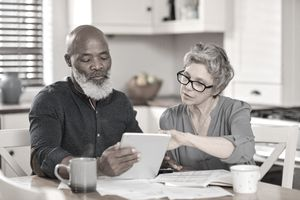 Senior couple using a digital tablet while going over bills and paperwork together at home