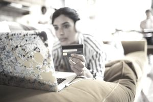 Woman laying on couch holding her credit card in front of her computer