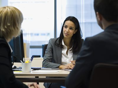 Female business executive speaks sitting at desk speaks to two colleagues