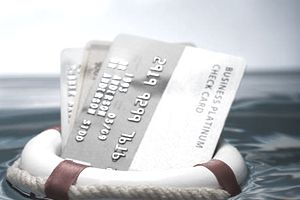 Credit cards keeping their balance in water held by a life preserver.