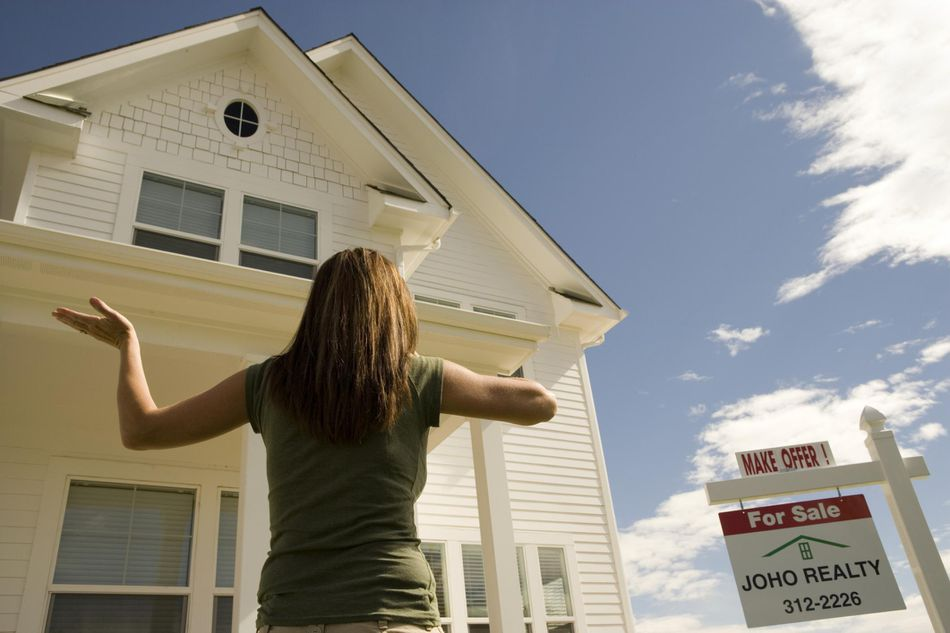 Woman standing in front of house for sale sign board, low angle view
