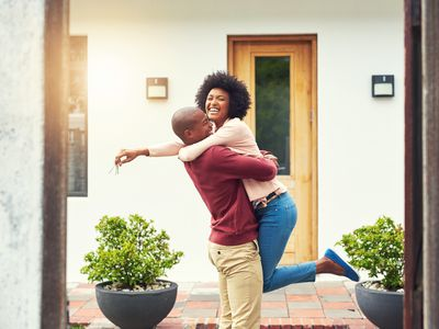 A woman jumps for joy into a man's arms in front of their new house
