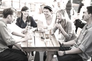 A group of friends enjoying a frugal gathering over drinks