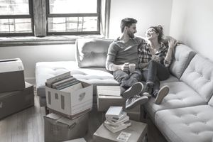 Young couple relaxing on sofa surrounded by moving boxes