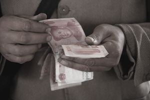 A vendor counts Yuan banknotes while waits for customers at a market in Huaibei, Anhui province