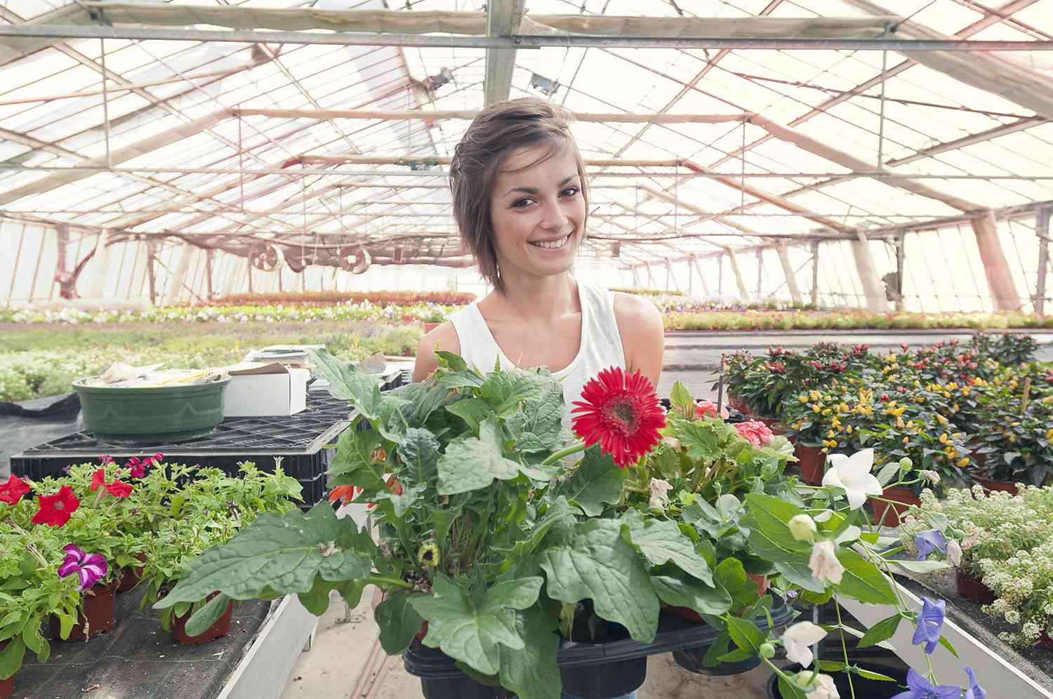 Young woman working part time in a greenhouse.