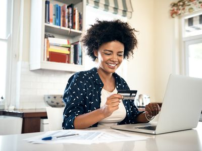 Woman smiles at credit card while sitting in front of a laptop