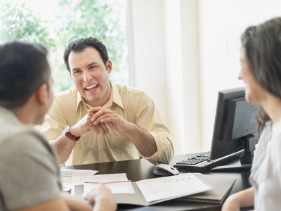 Banker talking to couple in his office as they open a checking account